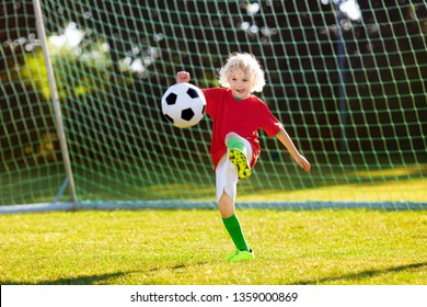 Kids play football on outdoor field. Portugal team fans. Children score a goal at soccer game. Boy in Portuguese jersey and cleats kicking ball. Football club pitch. Sports training for young player.