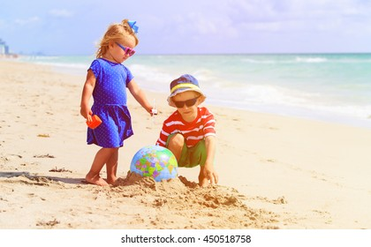 kids play with globe and toy plane on beach, travel concept