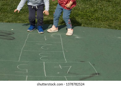 the kids play hopscotch at the park with sibling.