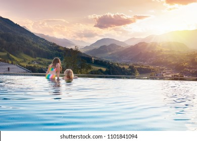 Kids play in outdoor infinity swimming pool of luxury spa alpine resort at sunset in Alps mountains. Spring or summer vacation for family with children. Boy and girl in hot tub with mountain view.