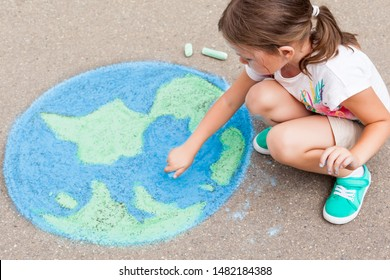 Kids play outdoors. Child girl draws a planet globe with a map of the world colored chalk on the pavement, asphalt. Earth, peace day concept.