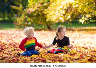 Kids play in  park. Children throwing yellow maple leaves. Boy and girl jump and run with oak leaf. Fall foliage.