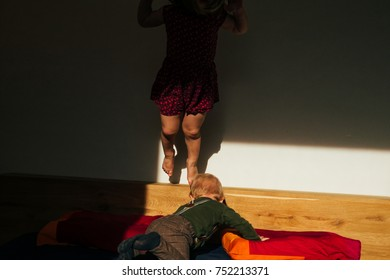 kids play together on a bed in a warm light