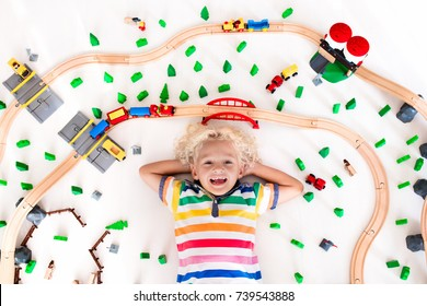 Kids play with toy train railway. Child playing with wooden trains. Toys for little boy. Preschooler building rail road and blocks at home or daycare, preschool. Kindergarten educational games.