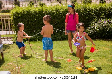 Kids play with  water in the garden at sunny summer day