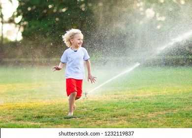 Kids play with water on hot summer day. Children with garden sprinkler. Outdoor fun. Boy and girl run on football field after training under water drops.