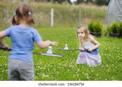 Kids playing badminton on beautiful summer day