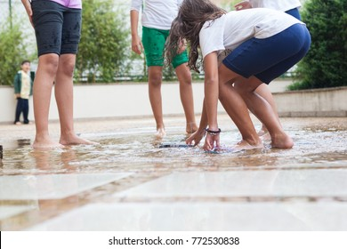 Kids playing barefeet on wet playground near water drain