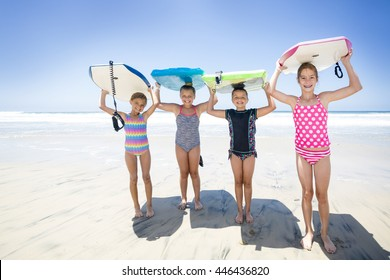 Kids playing at the beach together while on vacation holding their boogie boards