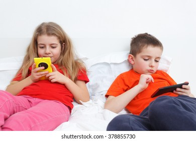 kids playing in bed with smartphone