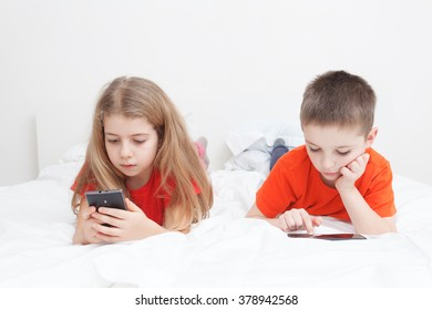 kids playing in bed with smart-phone