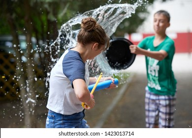 KIDS ARE PLAYING. BOY AND GIRL TEENAGERS DRAIN OTHER EACH OTHER WITH WATER