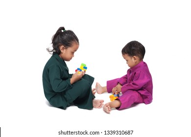 Kids playing with brick toys wearing traditional dress