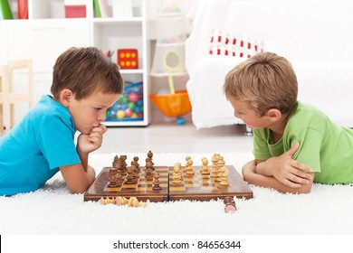 Kids playing chess laying on the floor and thinking intensely