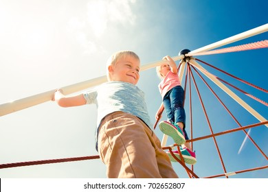KIDS PLAYING AND CLIMBING THE MONKEY BARS IN THE CITY PARK