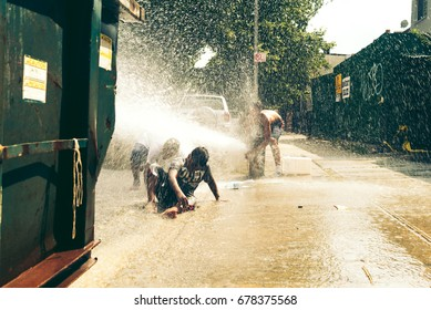 Kids playing with fire hydrant in the streets of Brooklyn, New York