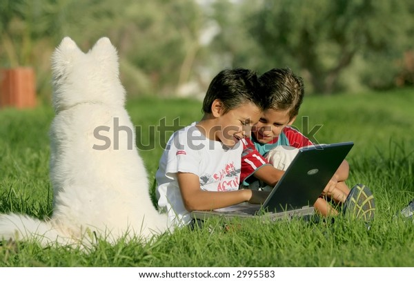 Kids playing games on laptop outdoor with dog