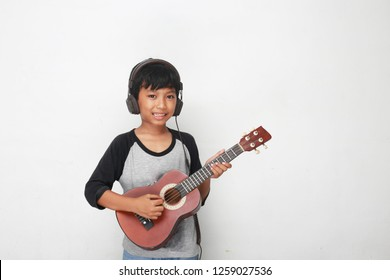 kids playing guitar. Smiling caucasian boy playing on acoustic guitar isolated on white background.