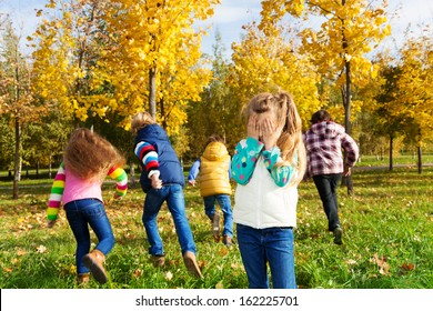 Kids playing hide and seek in autumn park