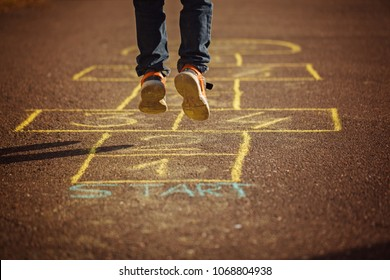 Kids playing hopscotch on playground outdoors. Hopscotch popular street game. Back view