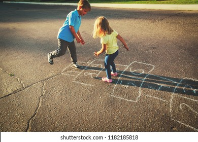 kids playing hopscotch on playground, outdoor activities