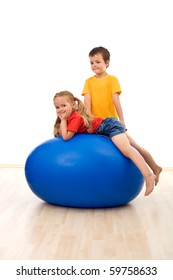 Kids playing with a large exercise ball in the gym - isolated