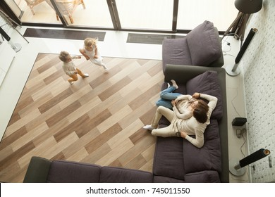Kids playing little boy and girl running in cozy living room interior while parents relaxing on comfortable sofa at home, happy family leisure activities in big house apartment with terrace, top view