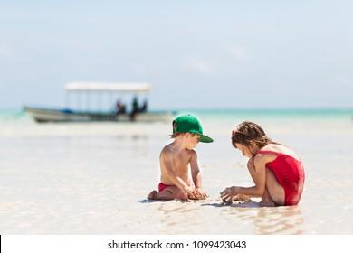 kids playing on beach. traveling with kids. paradise like seacoast on zanzibar. girl and boy enjoying summer vacation. family holidays on tropical island.