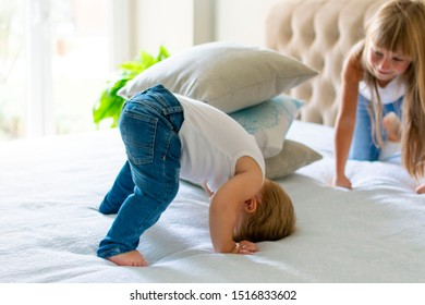 kids are playing on the bed.small baby boy staying upside down on the head and trying to tumble, bigger sister is watching him. happy childhood concept.