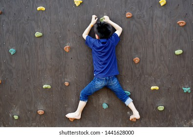 Kids playing on bouldering wall in park