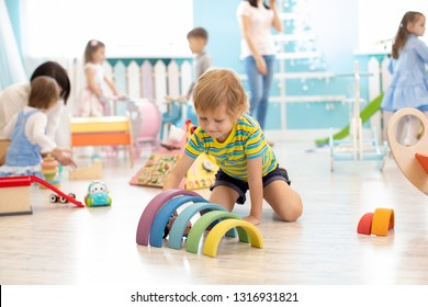 Kinder, die mit Lernspielzeug auf dem Boden spielen. Spielzeug für Vorschulen und Kindergarten. Kinder in Kindergarten oder Kinderbetreuung