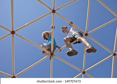 kids playing on monkey bars, view toward blue sky
