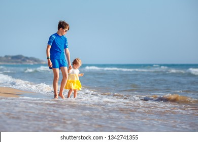 Kids playing on tropical beach. Big brother together with his little sister at sea shore at sunset. Family summer vacation. Children play with water. Ocean and island fun. Travel with young children