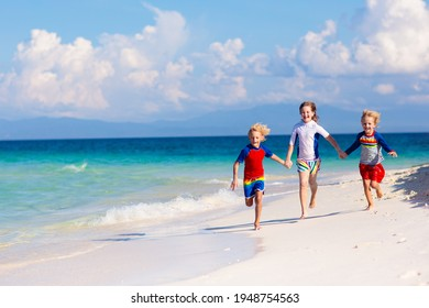 Kids playing on tropical beach. Children swim and play at sea on summer family vacation. Sand and water fun, sun protection for young child. Little boy and girl running and jumping at ocean shore.
