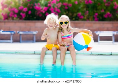 Kids playing at outdoor swimming pool. Little girl and boy play and swim in resort pool on tropical beach island summer family vacation. Swim and eye wear, sun protection, water toys for children