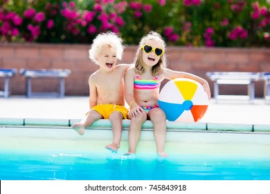 383160b456da7 Kids playing at outdoor swimming pool. Little girl and boy play and swim in  resort