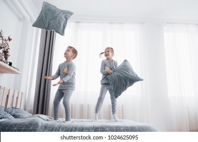 Kids playing in parents bed. Boy and girl in matching pajamas. Sleepwear and bedding for child, family morning.