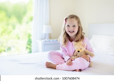 Kids playing in parents bed. Children wake up in sunny white bedroom. Little girl in pink pajamas. Sleepwear and bedding for child and baby. Nursery interior for toddler kid. Family morning.