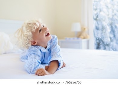 Kids playing in parents bed in winter. Children wake up in white bedroom by snow. Little boy in blue pajamas. Christmas sleepwear and bedding for child and baby. Family morning on snowy cold Xmas day.