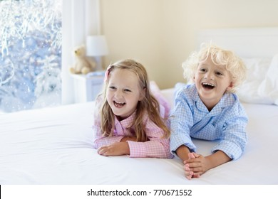 Kids playing in parents bed in winter. Children wake up in white bedroom by snow. Little boy and girl n pajamas. Christmas sleepwear and bedding for child and baby. Family morning on snowy Xmas day.