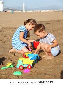 Kids playing with plastic toys on the beach