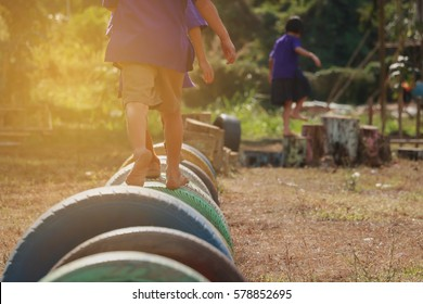 Kids playing in the playground. Running on tires.selective focus