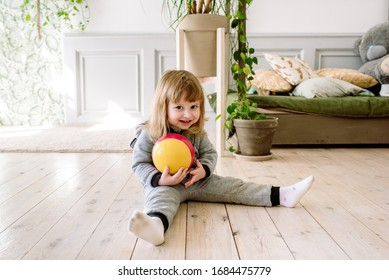 Kids playing in the room.Girl with a ball h in a bright living room on the floor. Childhood and family. Children games