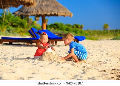kids playing with sand on summer tropical beach