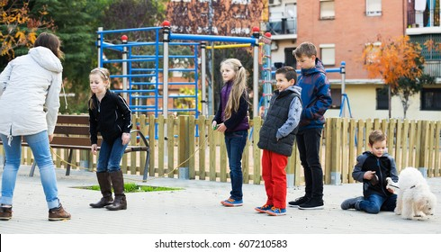 Kids playing skipping rope jumping game and laughing at street