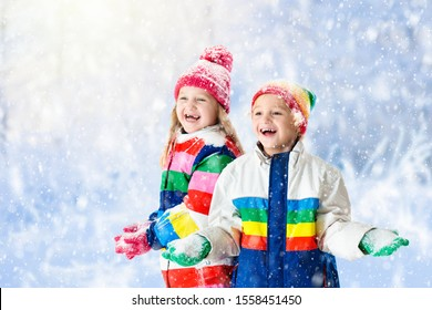 Kids playing in snow. Children play outdoors on snowy winter day. Boy and girl catching snowflakes in snowfall storm. Brother and sister throwing snow balls. Family Christmas vacation activity.