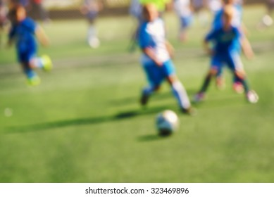 Kids playing soccer, defocussed blur sport background image