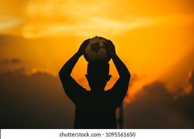 kids are playing soccer football for exercise under the sunlight. Silhouette and film picture style.
