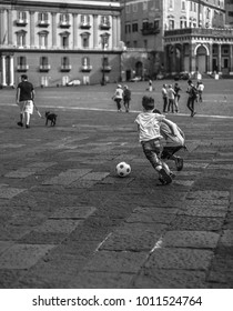 Kids playing soccer in a square of Napoli - Italy