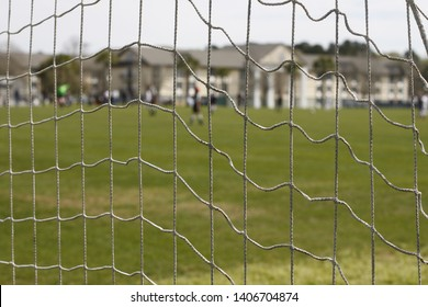 Kids playing soccer; view from behind the goalpost.